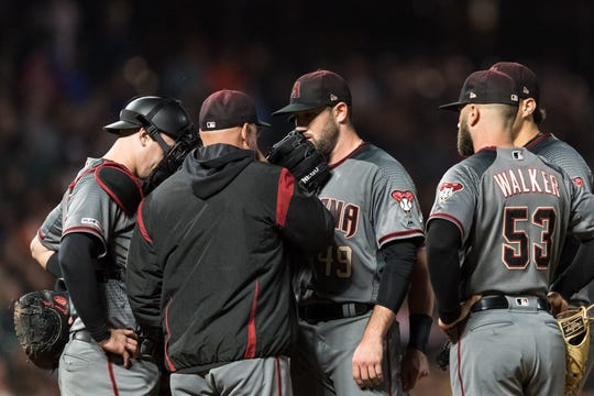 Diamondbacks pitcher Alex Young talks to pitching coach Mike Butcher during the fifth inning of a game Aug. 26 against the Giants at Oracle Park.