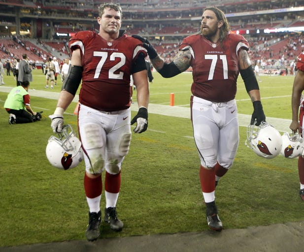 Cardinals offensive linemen Rich Ohrnberger (72)  and Daryn Colledge (71) walk off the field after a game against the 49ers at University of Phoenix Stadium on Oct. 29, 2012.