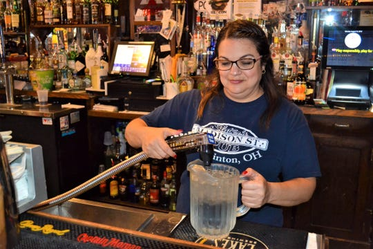 Sherry Depner, a server/bartender at Slater's Madison Street Pub, refills a water pitcher for customers. Depner said fishermen bring their fresh catch in every week so Slater's chef can cook it for them.