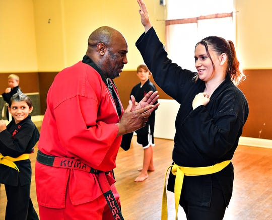 Wilmer Febus, 8, left, looks on as his mother, Brittany Wolf, 27, right, both of York City, raises her hand to answer a question asked by Grandmaster Wallace Kelly as he teaches a free martial arts class offered by Kelly's Universal Martial Arts at Yorktown Center in York City, Wednesday, Aug. 21, 2019. Dawn J. Sagert photo