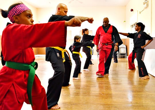 From right, Mi'Kel Kelly assists his father, Grandmaster Wallace Kelly as he teaches students Brittany Wolf, Wilmer Febus, 8, both of York City, Chuck Zienkiewicz, of Manchester Township, and sister, Kelce Kelly, 10, during a free martial arts class offered by Kelly's Universal Martial Arts at Yorktown Center in York City, Wednesday, Aug. 21, 2019. Dawn J. Sagert photo