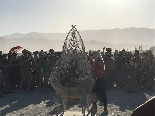 Burning Man co-founder Crimson Rose starts the ceremonial lighting of the fire that will spark the fire dancers' flames on Monday, Aug. 26 at Black Rock City in the desert outside Reno, Nevada.