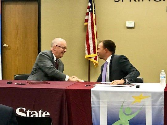 MSU President Clif Smart and Springfield Superintendent John Jungmann shake hands after signing an agreement to start the pilot program.