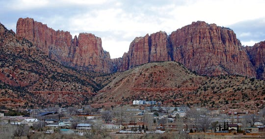 FILE - This Dec. 16, 2014, file photo, shows Hildale, Utah, sitting at the base of Red Rock Cliff mountains, with its sister city, Colorado City, Ariz., in the foreground. An appeals court has upheld a ruling that concluded two towns on the Arizona-Utah border had discriminated against people who weren't members of a polygamous sect, rejecting an argument that a judge made an error in finding there was a conspiracy between the church and towns. (AP Photo/Rick Bowmer, File)