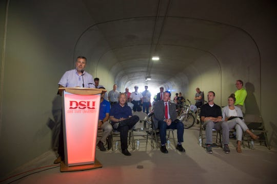 Community leaders celebrate the opening of Trailblazer Tunnel with a ribbon cutting and bike ride Tuesday, Aug. 27, 2019.