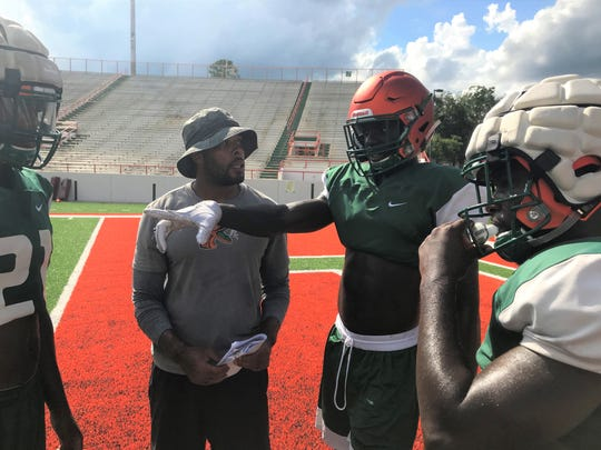 Safety Markquese Bell (center) goes over coverage with position coach Brandon Sharp. Bell is a former Under Armor All-American who transferred to FAMU from Coffeyville Community College in January.