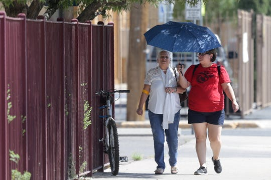 Irene Vasquez walks with her mother, Alicia Vasquez, through Downtown El Paso, hiding from El Paso's searing sun Tuesday, Aug. 27, 2019. Temperatures neared the 100-degree mark again.