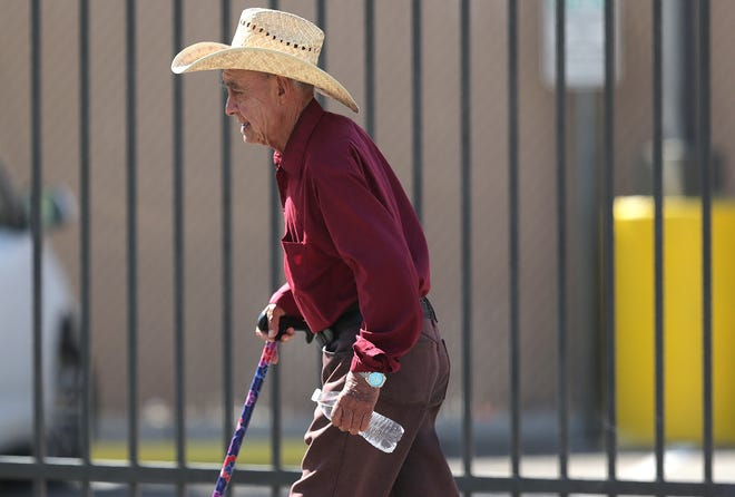 A man tries to beat the heat with a straw hat and bottled water as he makes his way to the border in Downtown El Paso on Tuesday, Aug. 27, 2019.