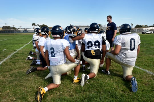 "Santa Clara High head coach Michael Laubacher speaks with his team during a recent practice. The program has switched from 11-man to 8-man football. ""It's essentially the same. You're just losing a couple guys off the field,"" Laubacher says of the change."