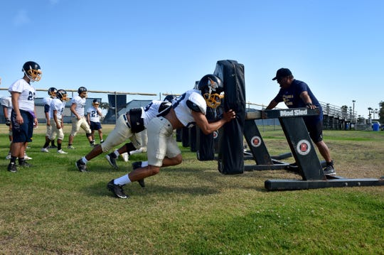 Santa Clara High's Leo Porras and his teammates hit the blocking dummy during a recent practice. Santa Clara has had to adjust being an 8-man football program.