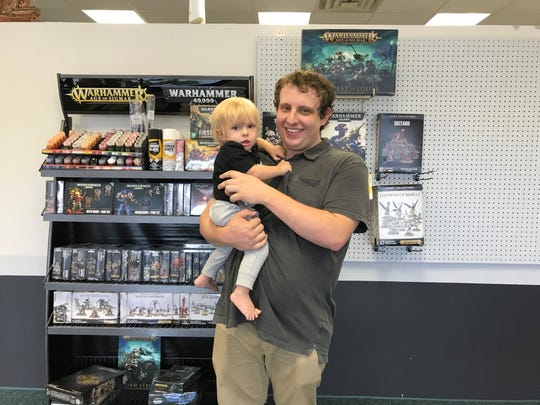 Owner John Brown with his son Henry Odin Brown pose at his new store, Odin Games and Hobby. The game shop is named after John Brown's son.