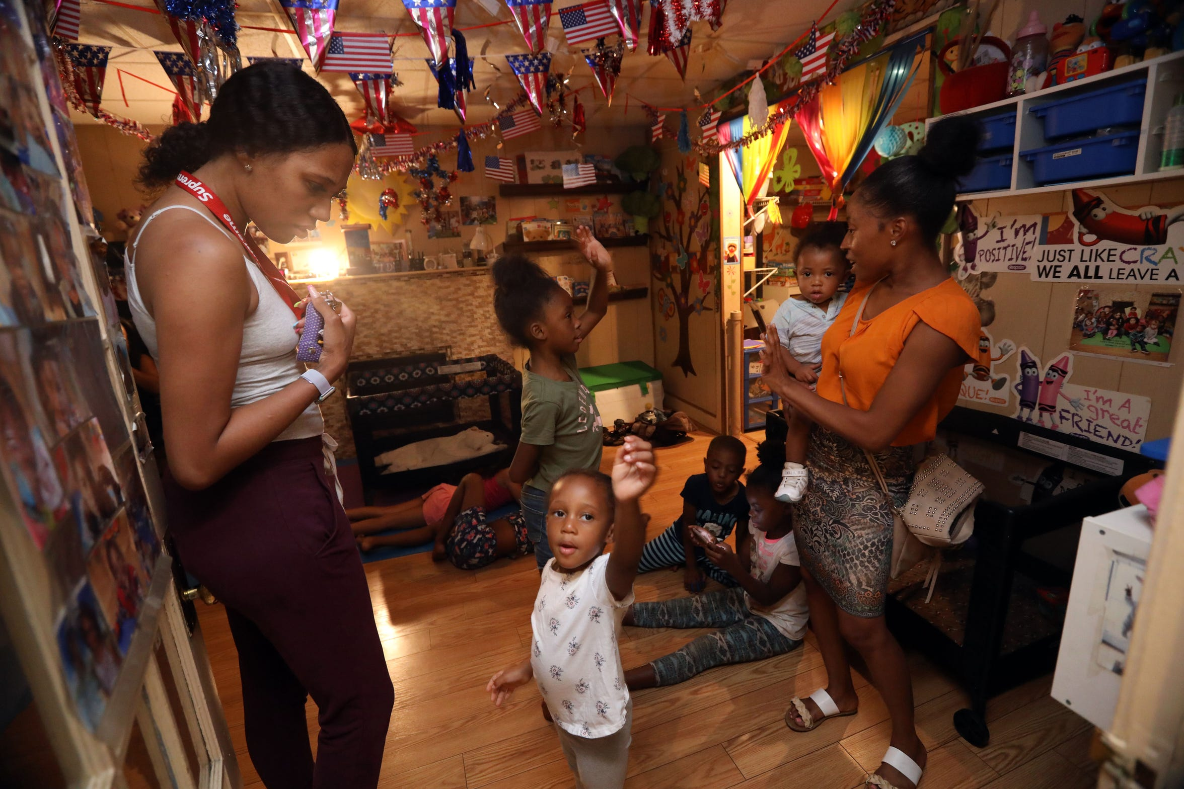 Brittney Foster, left, and Chanelle Hall pick up their children at Dee's Tots Child Care in New Rochelle after working evening shifts Aug. 15, 2019. The family-run day care offers late and overnight care for children whose parents work late hours.