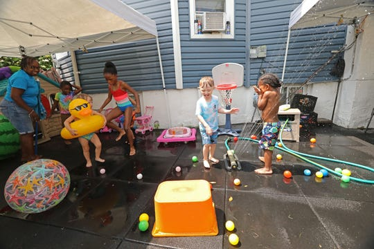 Children play in the sprinklers at Dee's Tots Child Care in New Rochelle Aug. 8, 2019. The family-run day care also offers late and overnight care for children whose parents work late hours.