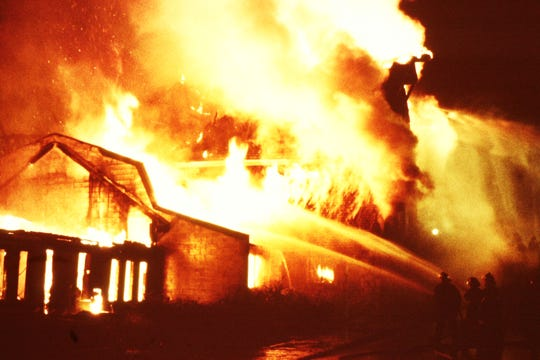 Firefighters from several Putnam and Northern Westchester fire departments assist Carmel firefighters in battling a spectacular blaze that destroyed several building at The Barns Medical Offices in Carmel July 21, 1990.