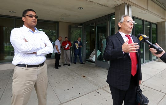 Former Spring Valley building inspector Walter Booker looks on as his attorney Michael Sussman speaks to members of the media after his sentencing Aug. 27, 2019 at Rockland County Court in New City. Booker was sentenced to five years probation on his conviction involving the issuance of false certificate that aided a homeowner operating two childcare operations out of his house.