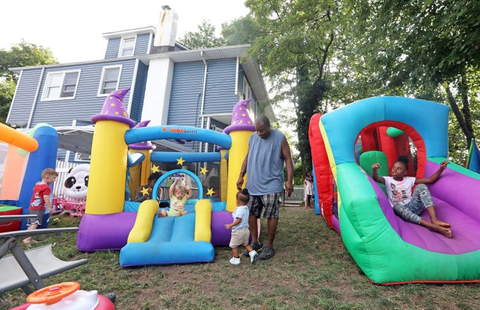 """Patrick Hogan, known as """"Pop Pop,"""" watches after children playing in the bounce houses at Dee's Tots Child Care in New Rochelle Aug. 15, 2019. Hogan and his wife Deloris run the day care. They also offer late and overnight care for children whose parents work late hours."""
