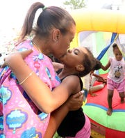 Shanona Tate kisses her daughter Naima Harrell, 8, goodbye after dropping her off at Dee's Tots Child Care in New Rochelle Aug. 15, 2019. Tate, a registered nurse that works the overnight shift, leaves her kids overnight at the Dee's Tots when working.