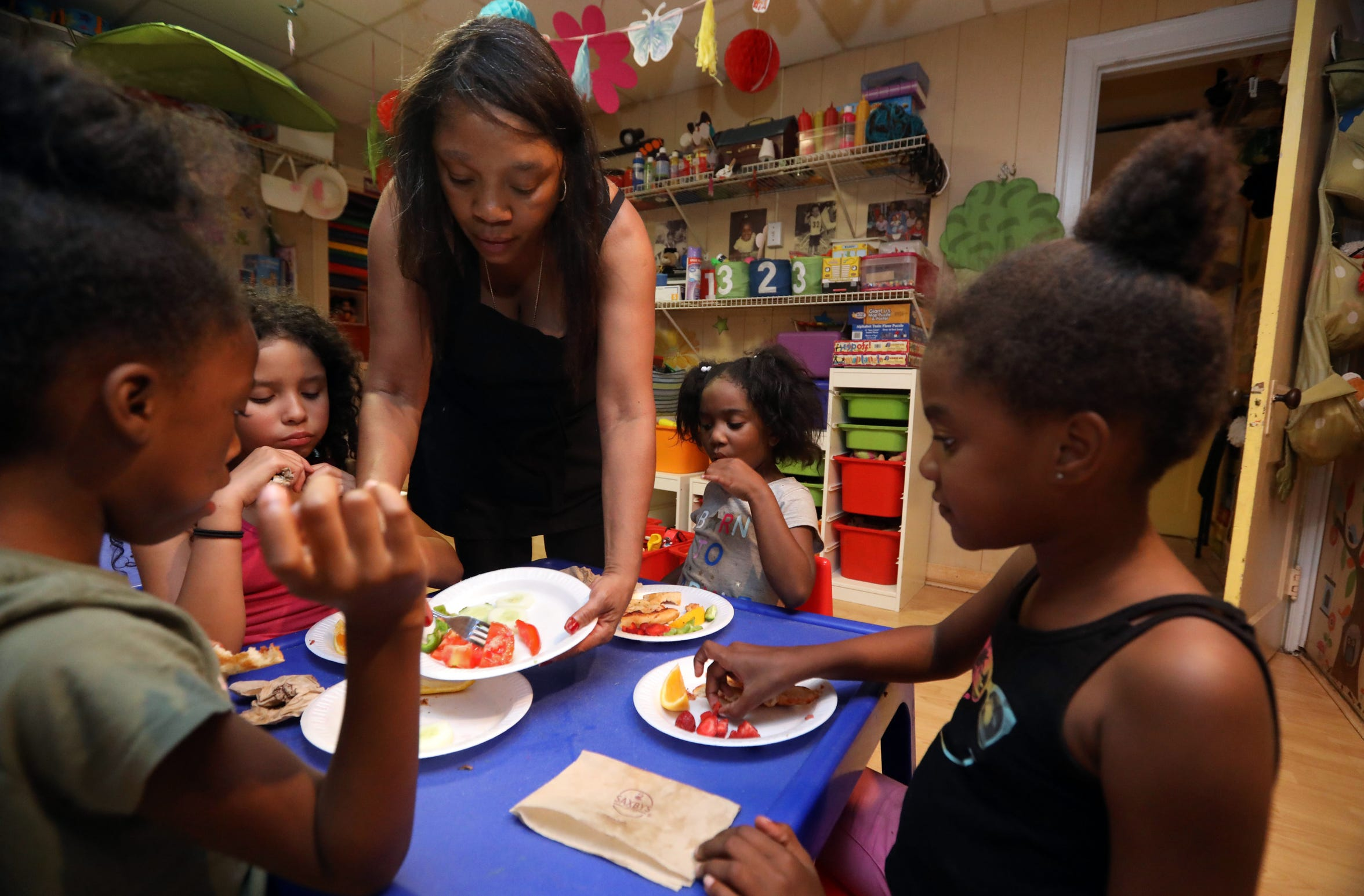 """Deloris Hogan, known as """"Nunu,"""" serves dinner at Dee's Tots Child Care in New Rochelle Aug. 15, 2019. Hogan and her husband Patrick run the day care. They also offer late and overnight care for children whose parents work late hours."""