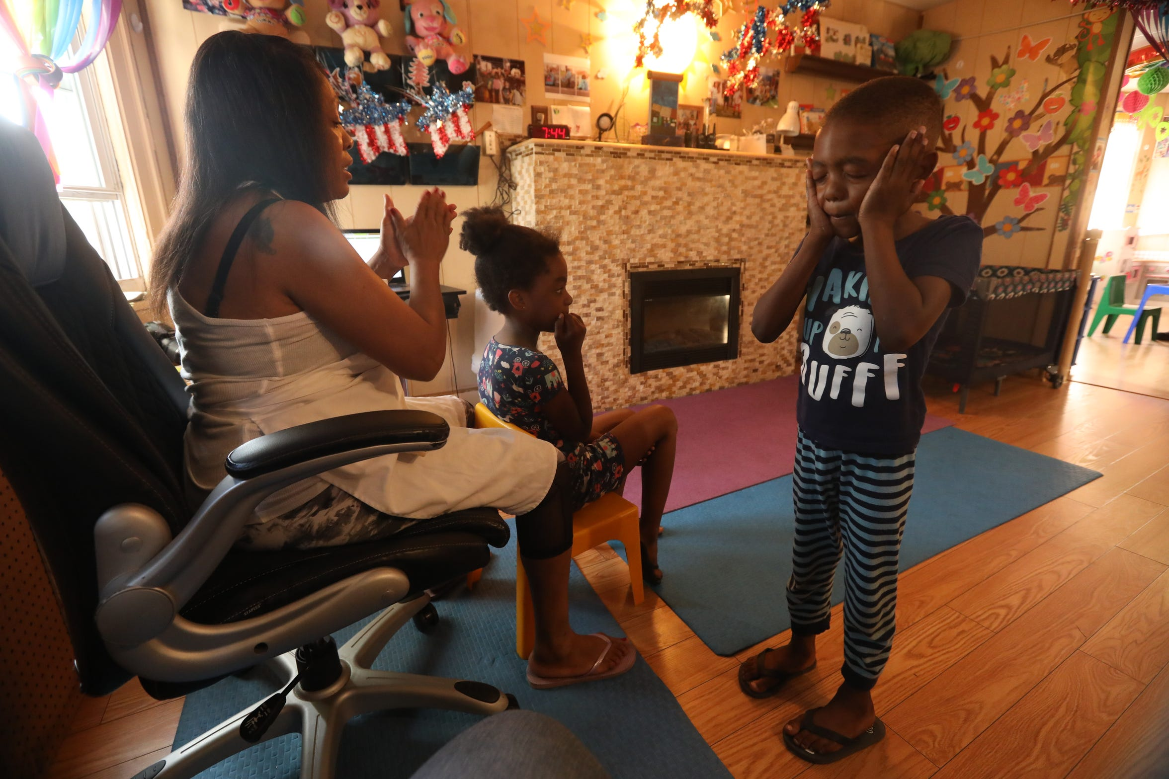 """Deloris Hogan, known as """"Nunu,"""" gets Naima Harrell, 8, and her brother Noah Harrell, 6, ready for the day after they spent the night at Dee's Tots Child Care in New Rochelle Aug. 16, 2019. The siblings stay overnight when their mother, a registered nurse, works the overnight shift."""