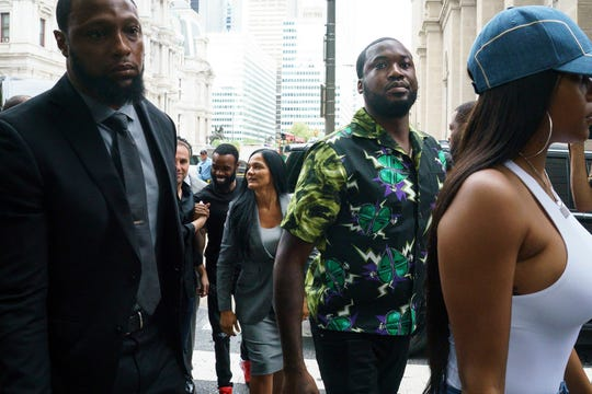 Rapper Meek Mill, center, arrives at the Criminal Justice Center in Philadelphia on Tuesday, Aug. 27, 2019.  Mill will learn if Philadelphia prosecutors will drop a 2007 case that's kept him under court supervision for more than a decade. (Jessica Griffin/The Philadelphia Inquirer via AP)