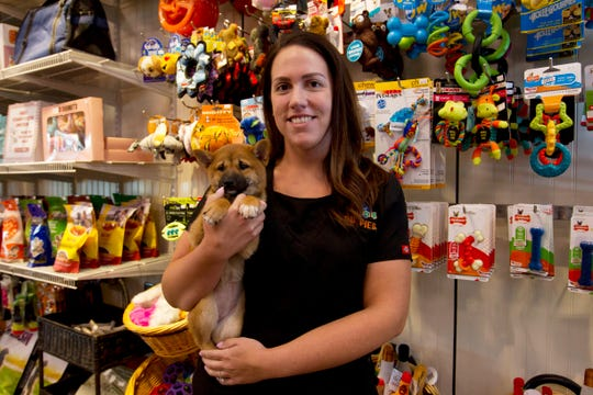 "Charm City Puppies manager Becky Schmidt poses with a puppy at a pet store in Columbia, Md., Monday, Aug. 26, 2019. Pet stores are suing to block a Maryland law that will bar them from selling commercially bred dogs and cats, a measure billed as a check against unlicensed and substandard ""puppy mills."" Schmidt, whose Columbia store is one of the plaintiffs, said it only uses breeders that are ""quality-inspected"" and federally regulated. ""If anything, if our doors close, it's going to force consumers to have to go to the unregulated, uninspected sources,"" she said Monday."