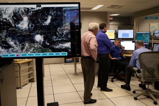 Jamie Rhome, storm surge specialist, seated, monitors the progress of Tropical Storm Dorian at the National Hurricane Center, Tuesday, Aug. 27, 2019, in Miami.