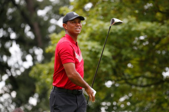 Tiger Woods  hits his tee shot on the fourth hole during the final round of the BMW Championship golf tournament at Medinah Country Club .