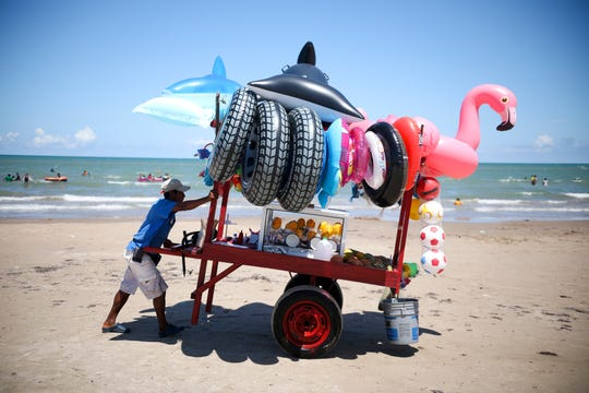 In this Aug. 3, 2019 photo, a vendor pushes his cart equipped with inflatable pool toys and fruit cups along the shoreline of Playa Bagdad near the border city of Matamoros, Mexico. Locals view it as a place where it is best to keep out of trouble.