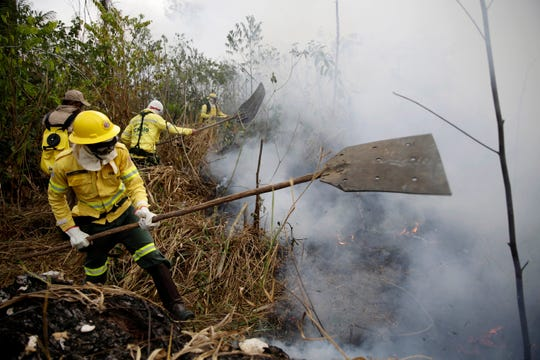 Firefighters work to put out fires along the road to Jacunda National Forest, near the city of Porto Velho in the Vila Nova Samuel region which is part of Brazil's Amazon on Aug. 26, 2019.