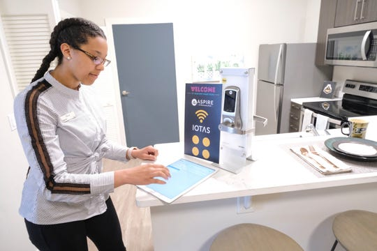 Leasing Specialist Olivia West demonstrates smart apartment technology called IOTAS that will be available in each unit of Aspire at Discovery Park apartments in West Lafayette, Ind., adjacent to Purdue University. West will live in the complex and received a discount on her rent as an employee.
