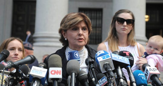 Attorney Gloria Allred, center, flanked by two clients who are Jeffrey Epstein accusers,  speaks during a news conference after leaving a Manhattan federal court where victims of the wealthy financier who died in jail addressed a hearing on whether the sex trafficking charges against Epstein should be dismissed.Tuesday Aug. 27, 2019 (AP Photo/Bebeto Matthews)