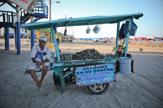 In this Aug. 2, 2019 photo, an oyster vendor snacks on shelled peanuts while he waits for customers in Playa Bagdad near the border city of Matamoros, Mexico. Here, the landscape is not one of walls or border guards; it is simply miles of dunes and Gulf coast beaches, marked only by simple wooden huts or awnings held up by sticks.