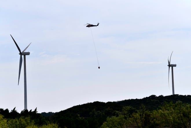 A helicopter flies toward a stock tank after dropping water on the smoldering remains of the Rhodes Ranch 3 Fire in Mulberry Canyon Tuesday.