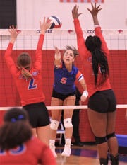 San Angelo Central's Mya Moore (5) hits between Cooper's Haley Riley (2) and Dazz Larkins. Central beat the Lady Cougars 27-25, 21-25, 25-15, 25-19 in the nondistrict match Tuesday, Aug. 27, 2019, at Cougar Gym.