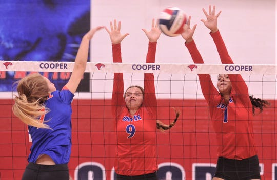 Cooper's Alissa Montgomery (9) and Diamond Brown defend at the net as San Angelo Central's Steely Poss hits the ball. Central beat the Lady Cougars 27-25, 21-25, 25-15, 25-19 in the nondistrict match Tuesday, Aug. 27, 2019, at Cougar Gym.