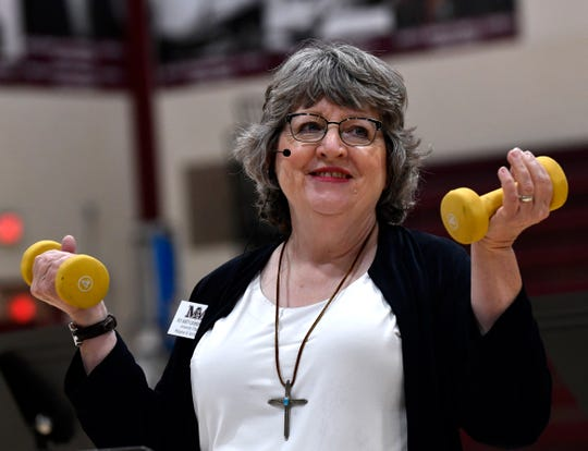 McMurry University Chaplain Marty CashBurless uses hand weights as a prop while addressing students during convocation Tuesday. Her message to students: Be strong in your faith.