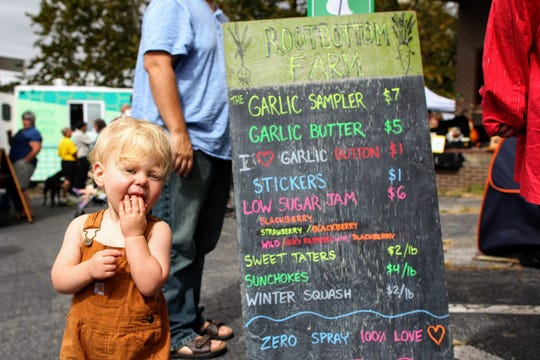 A young garlic fan samples the wares at WNC Garlic Fest.
