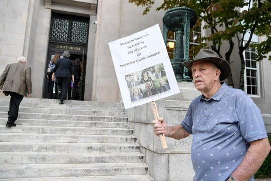 John Payne, of Waynesville, holds a sign calling for maximum sentences for corrupt Buncombe County officials as Michael Greene arrives at the Federal Courthouse in Asheville August 28, 2019.