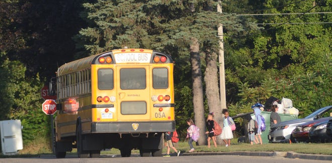 Children climb on the school bus in Marshall on Wednesday.