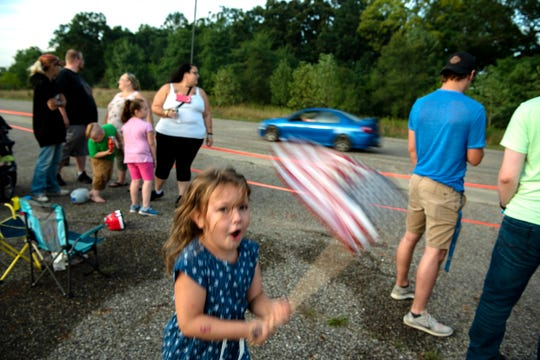 Kamila Durant, 6, waves an American flag during AutoMODIFIED's drag races on Sunday, Aug. 25, 2019 in Battle Creek, Mich. The lot is owned by Prairie Farms and is shifting management, so the car club must find a new space to race their vehicles.