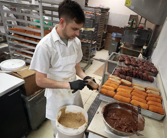 Eric Noga ices maple and chocolate bars in the kitchen of Larry and Kristi's Bakery in Bremerton on Wednesday, August 28, 2019.