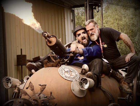 "Elton Busby, also known as Poppy, left, and Michael Kerkes, right, ride a zombie-fighting ""steam-punk mobile"" created by local artist Ray Hammar. Hammar's studio is the staging ground for the Gorst Underground Film Festival."