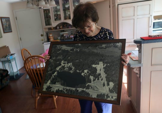 Harriet Higdon looks over an aerial photograph of Lake Emelia dated June 30, 1977, at her Port Orchard home. Higdon's parents, Herb and Hilda Goerz, established the manmade lake and set the stage for a community of homes surrounding it.