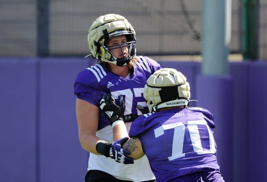 Washington's Trey Adams, left, pushes against Jared Hilbers during a drill at an NCAA football practice Tuesday, Aug. 6, 2019, in Seattle.