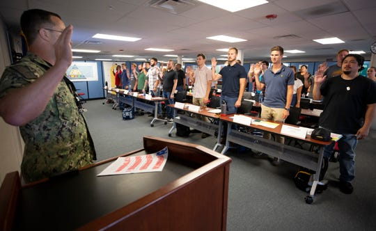 Capt. Kenneth Shepard, production resources officer at Puget Sound Naval Shipyard & Intermediate Maintenance Facility, administers the federal employees' oath of office to new shipyard hires during the weeklong new employee orientation.