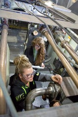 In a shipboard compartment mock-up at Puget Sound Naval Shipyard, helper-trainee Sarina Wolf, foreground, trains on disassembly of a union joint under the watchful eye of marine pipefitter Samantha King, a work leader and subject matter expert. Wolf has worked at the shipyard six months.