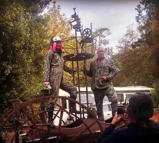 """Filmmaker Ethan Minkser, right, and Aura Stiers, left, climb aboard local artist Ray Hammar's """"steam-punk mobile."""""""