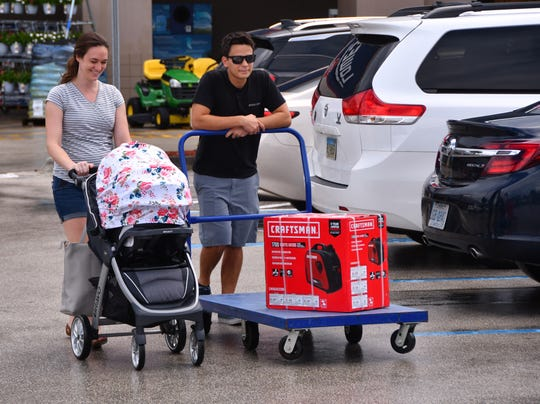 Alex and Whitney Dacquel of Viera with their  three day old daughter Avery wheel one of the last generators out of Lowe's in Rockledge on Wednesday. Lowe's is expecting another truck of water, generators, plywood and propane.