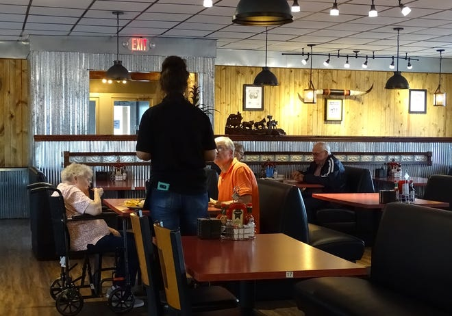 Waitress Sarah Davis checks on a table at the Rusty Horseshoe in Galion on Tuesday. The new restaurant had its grand opening on Wednesday.
