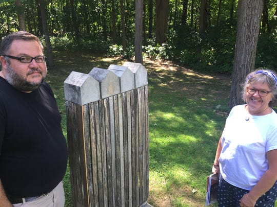 """Ric Kasini Kadour, curator of contemporary art at the Rokeby Museum in Ferrisburgh, and museum director Catherine Brooks stand next to Ferrisburgh artist Denis Versweyveld's work """"Four Old Houses"""" outside the museum's education center on Aug. 27, 2019."""